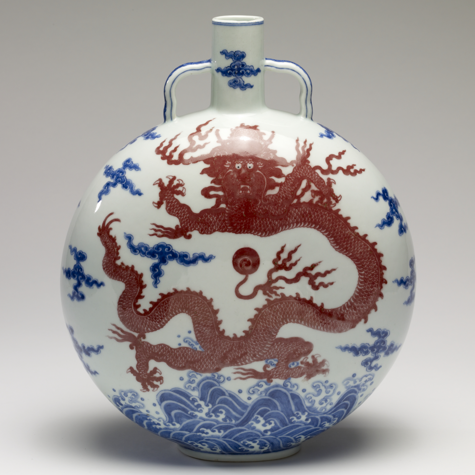 white vase with red and blue dragon motif