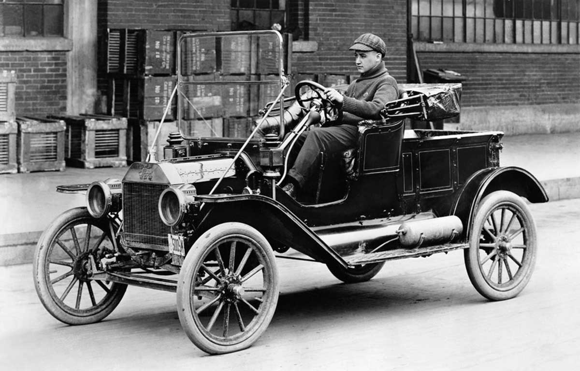 black and white picture of a man driving model T car
