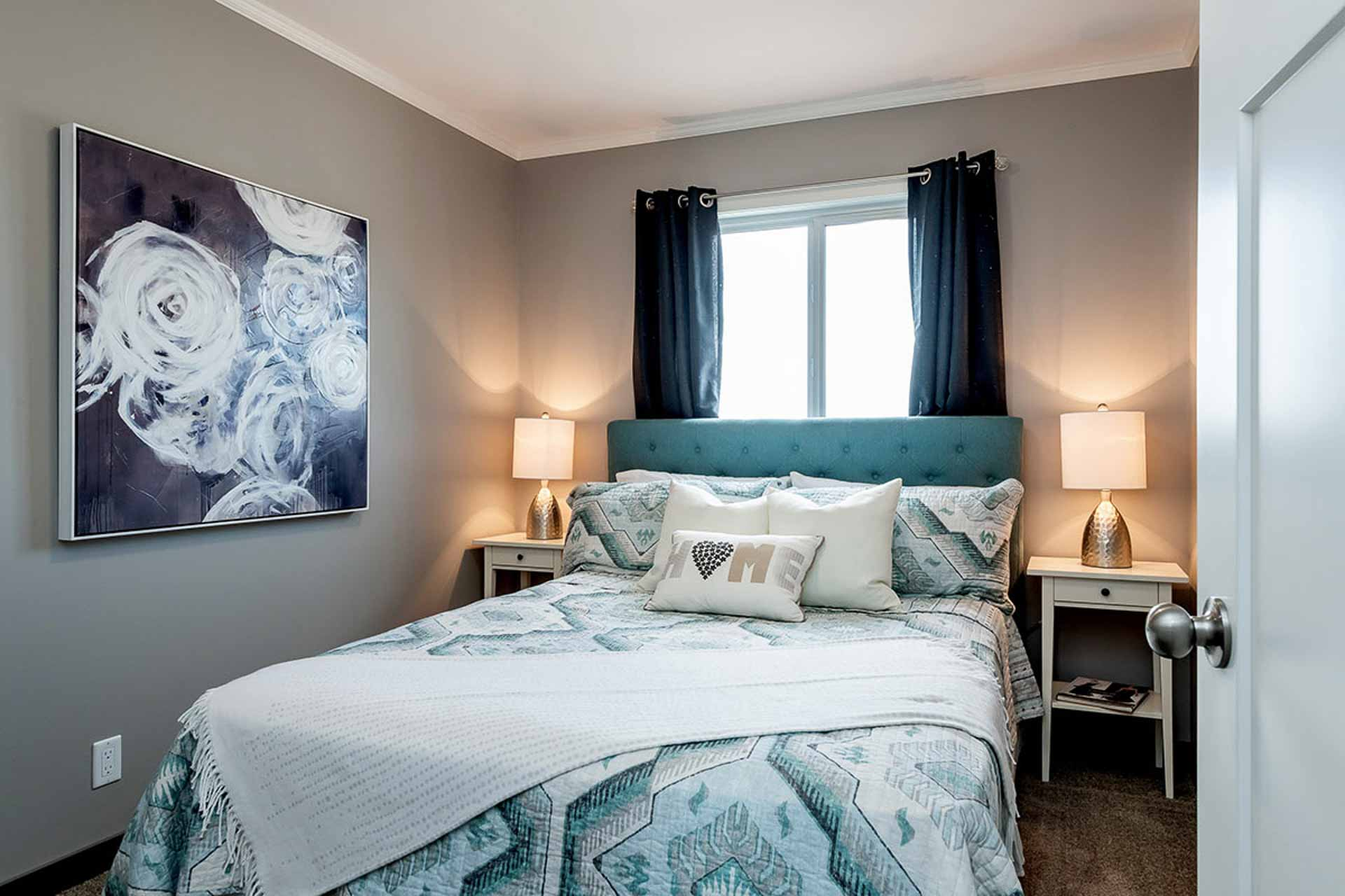 A bedroom with grey walls and a bed with a blue headboard and lots of pillows.