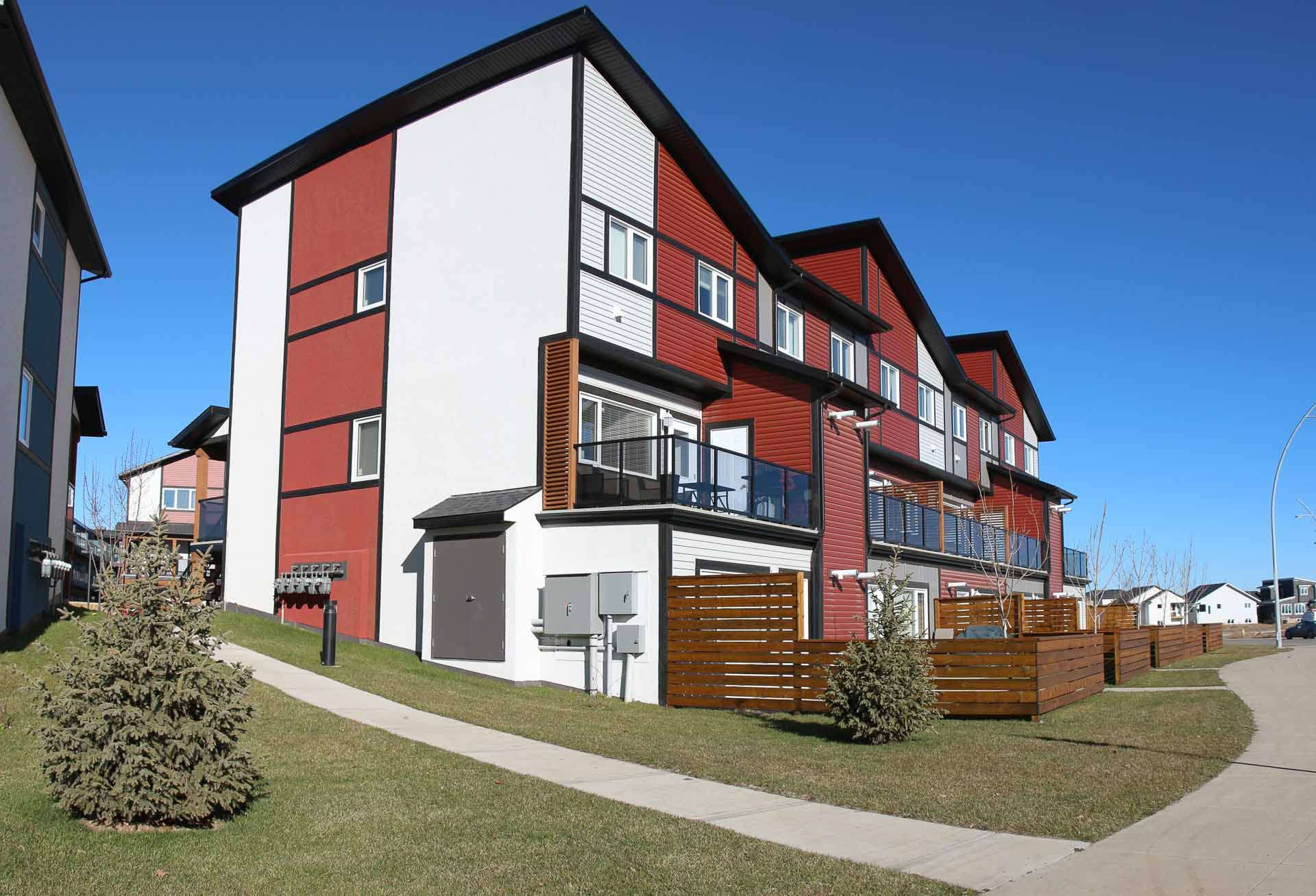 A multi-family residential building with red and white siding and fenced semi-private yards. In Saskatoon, Sask.