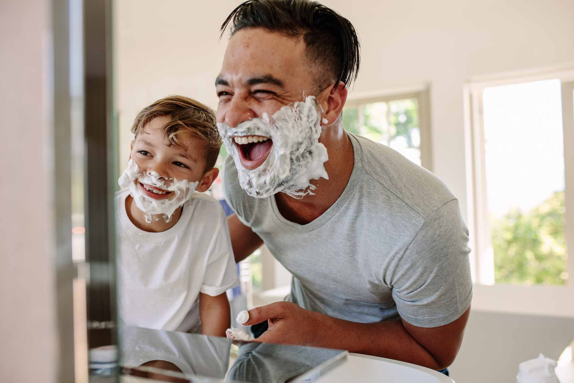 Dad and son laughing while putting shaving cream on their faces and looking in the mirror.