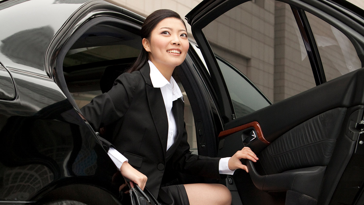 Businesswoman exiting her chauffeured car.