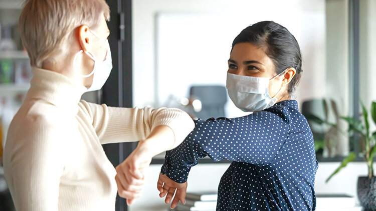 Two women, wearing face masks, greet each other in an office by bumping elbows.