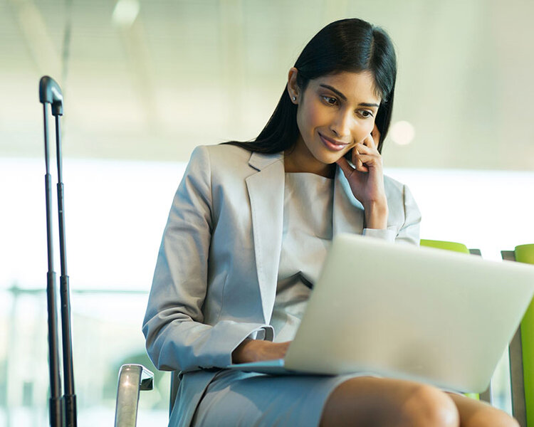 Businesswoman sitting in airport waiting area and working on laptop.