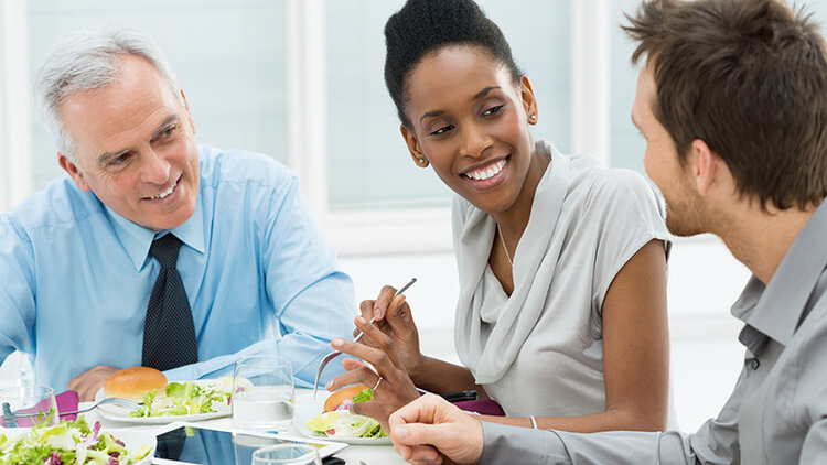 Business colleagues sharing a meal while working.