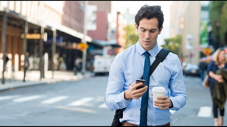 Image: A businessman wearing a blue shirt and tie, walking on a city street, holding a coffee cup and looking at cell phone.