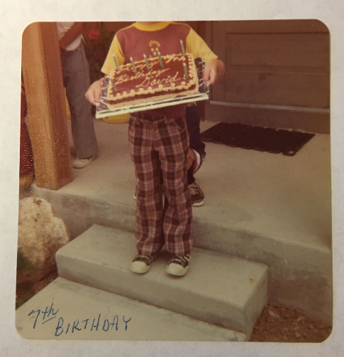 """A an aged photo of Dave's seventh birthday; a child dressed in 1970s style, yellow and brown t-shirt and plaid pants, holding a sheet cake with candles that says """"Happy Birthday David,"""" but the child's entire head is cropped out of the top of the photo."""