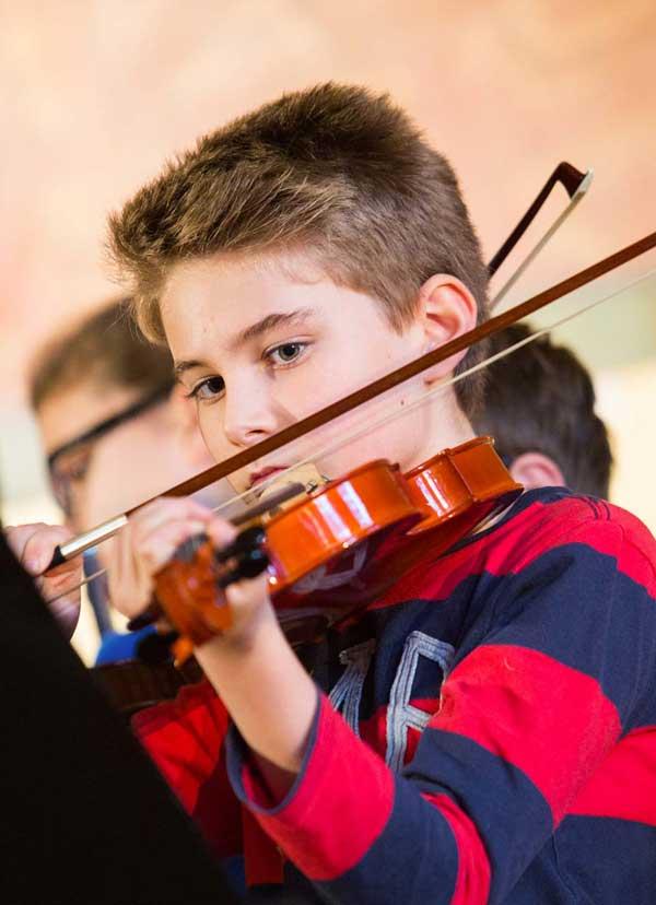 Garçon de l'école Koenig jouant de la musique de violon
