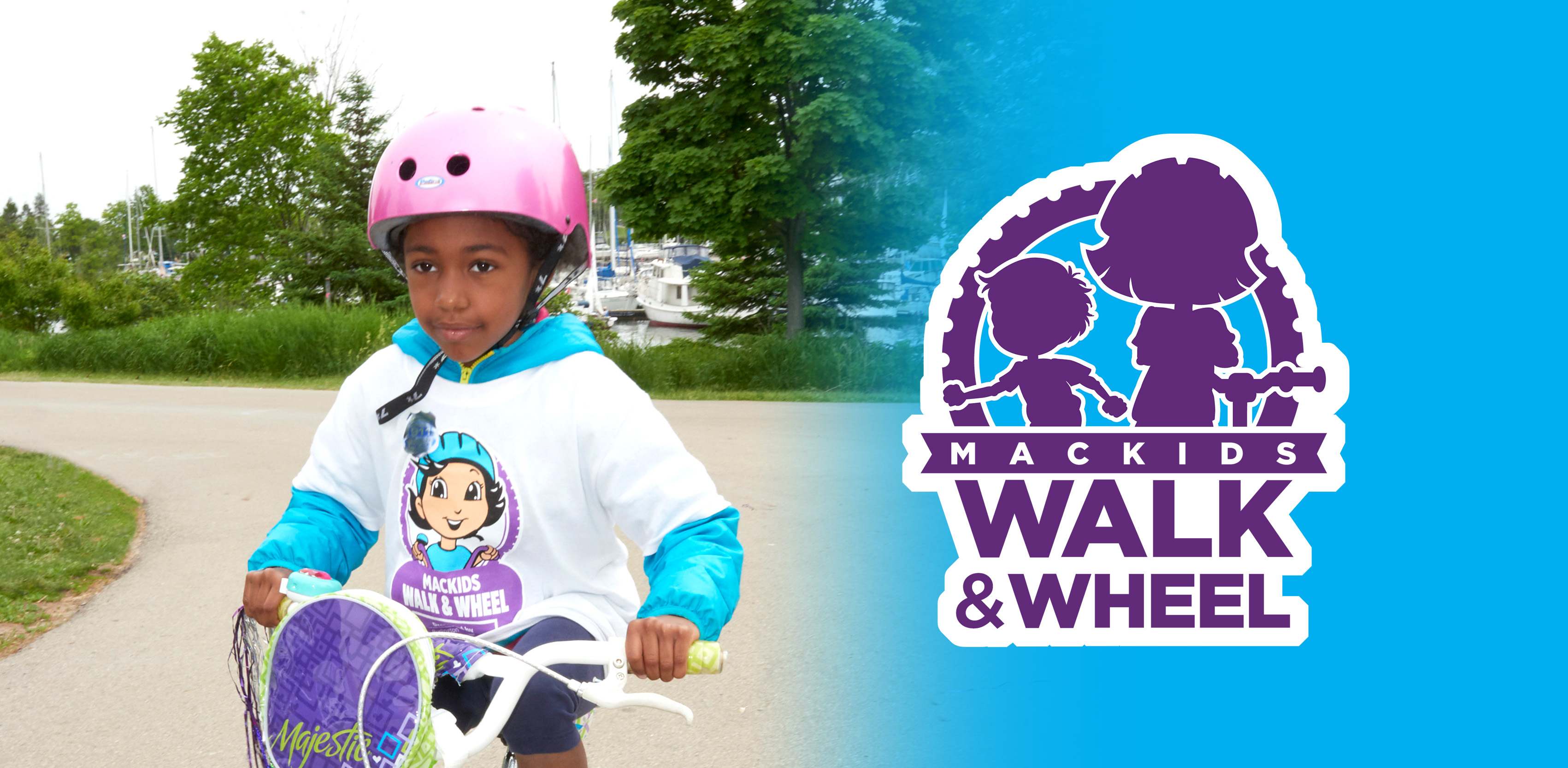 A child in a Walk and Wheel t-shirt rides her bike