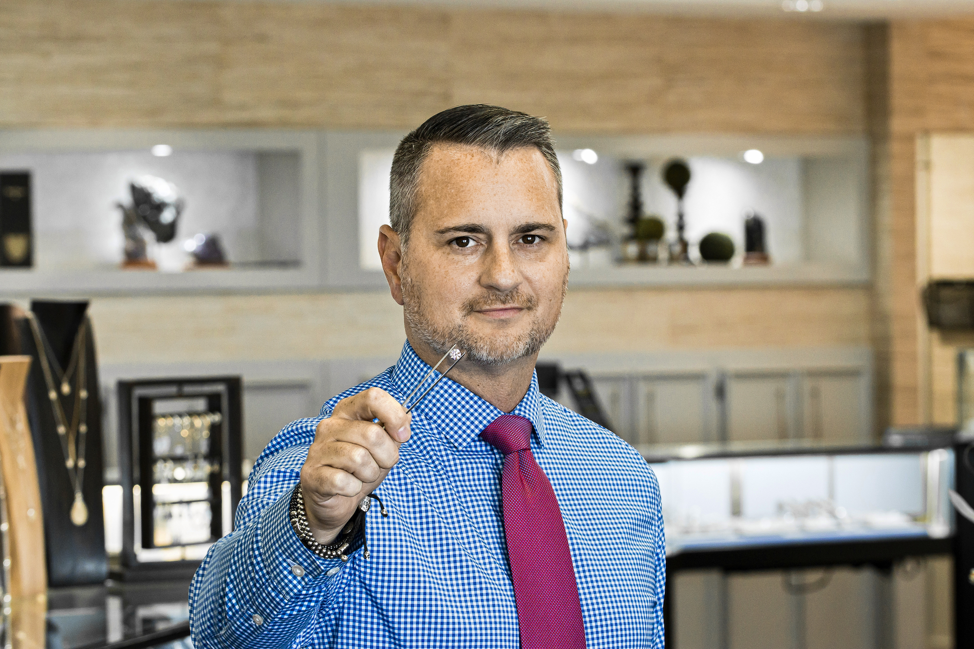 CEO John Carter holding a diamond between a set of tweezers with the store in the background