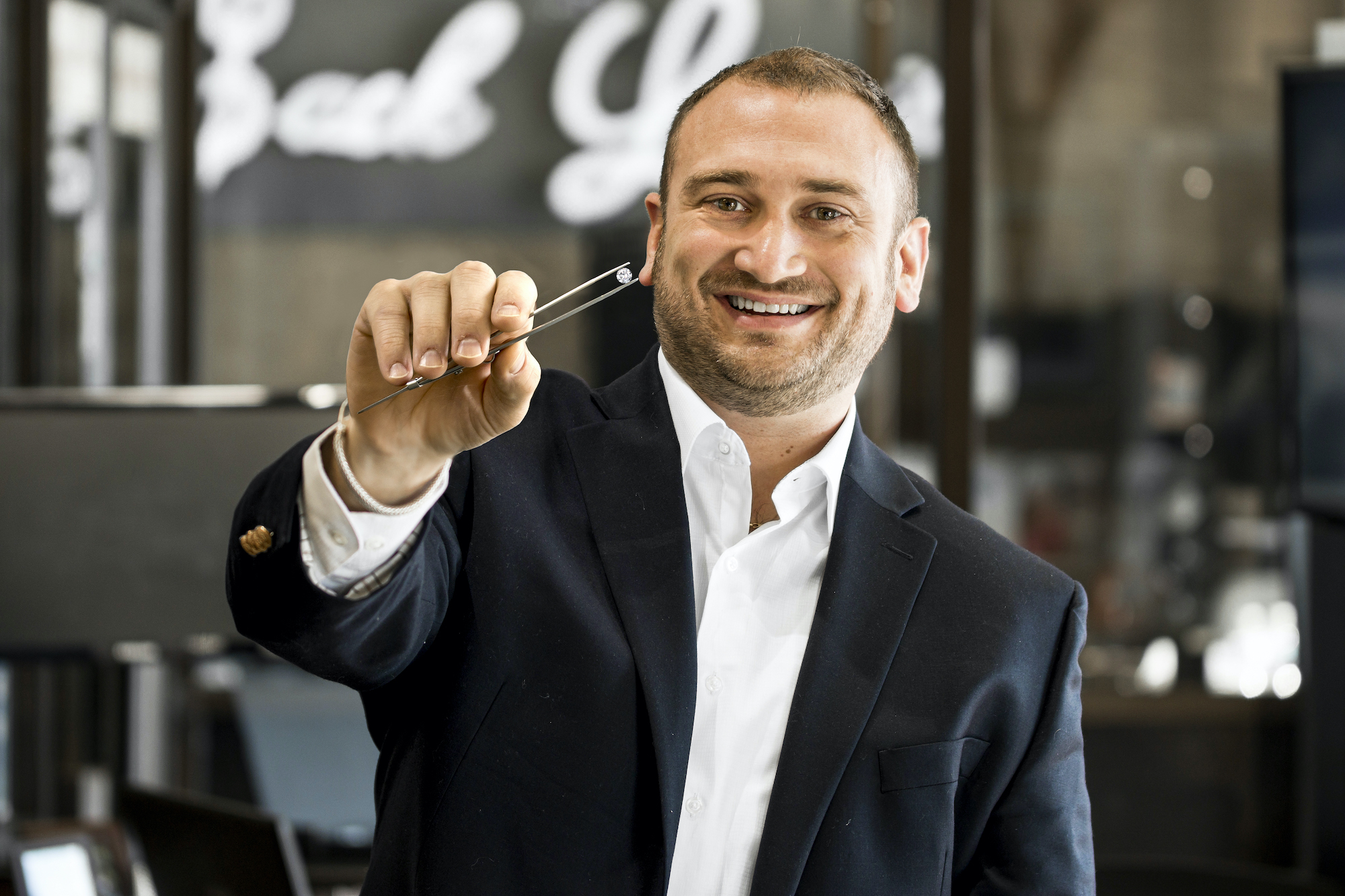 sales associate Brooks smiling at the camera while holding a round diamond with a pair of tweezers