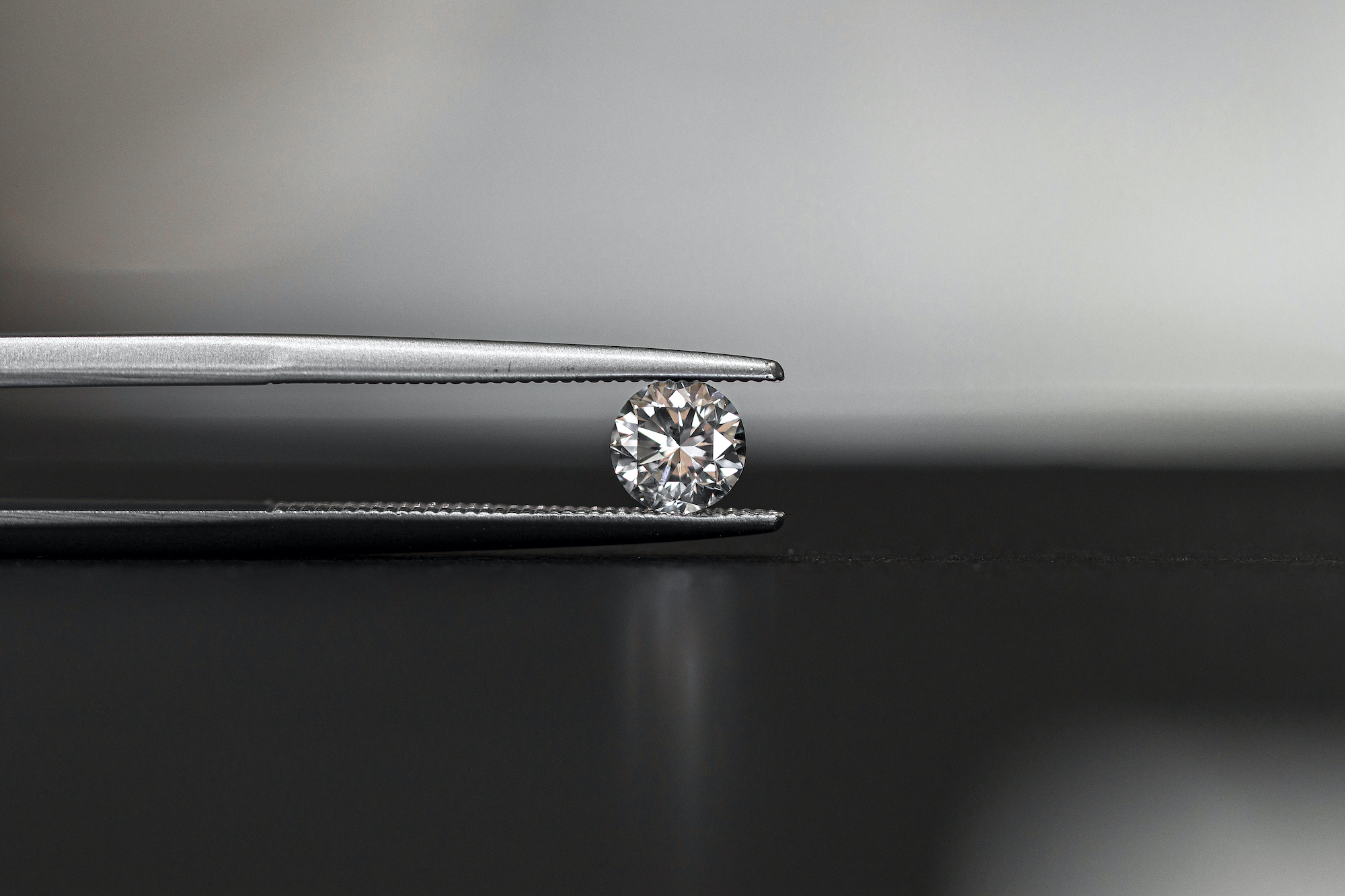round diamond being held by a pair of tweezers over a reflective table