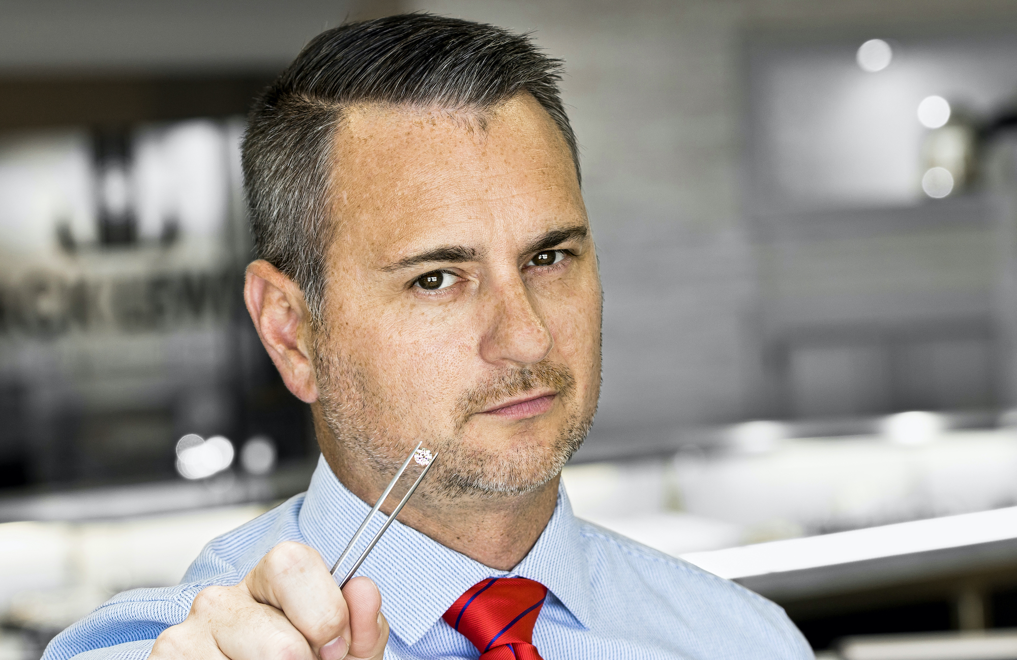 CEO John Carter looking straight into the camera holding a round diamond with a set of tweezers with the interior of the store in the background
