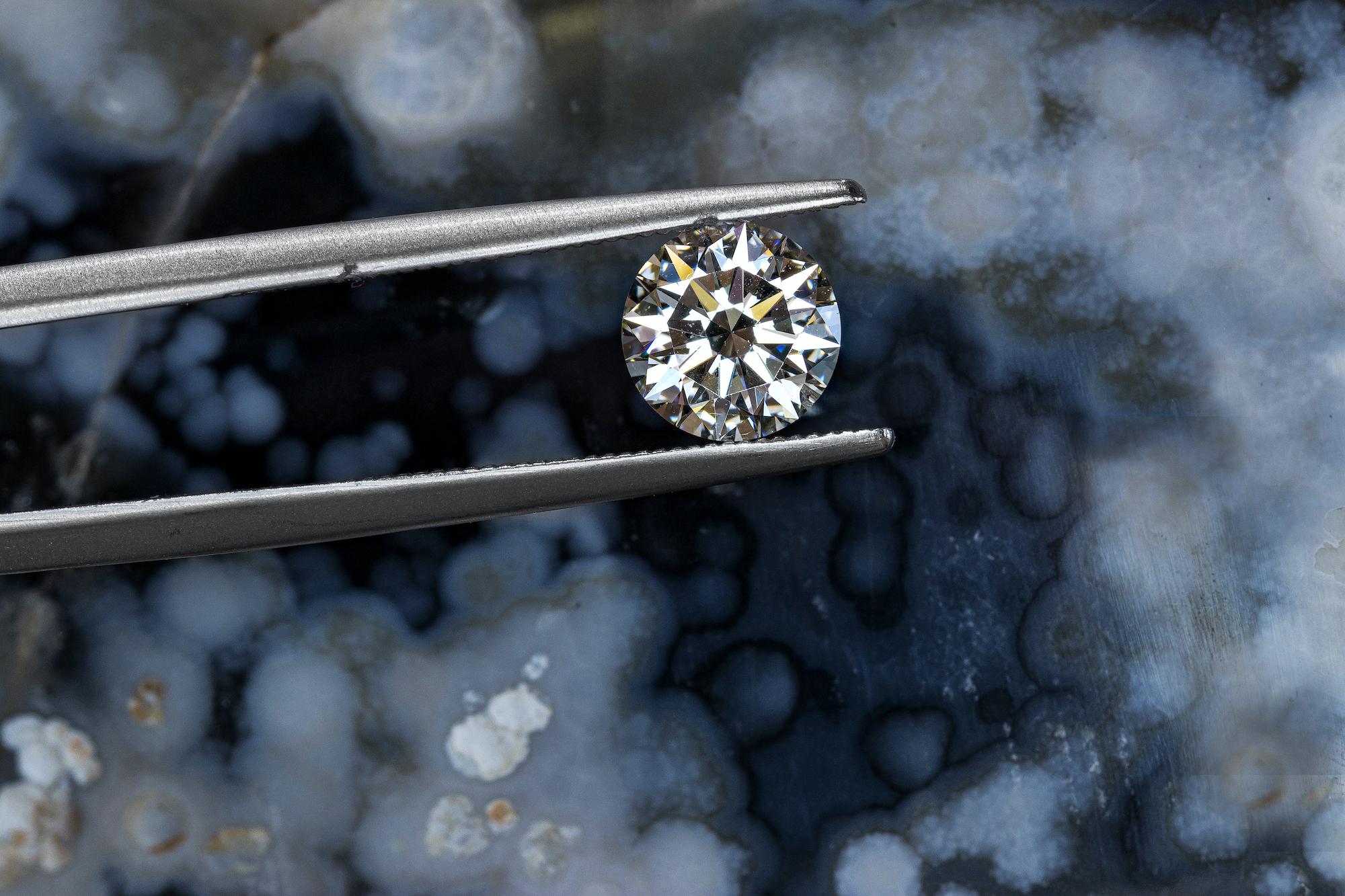 round diamond being held by a pair of tweezers
