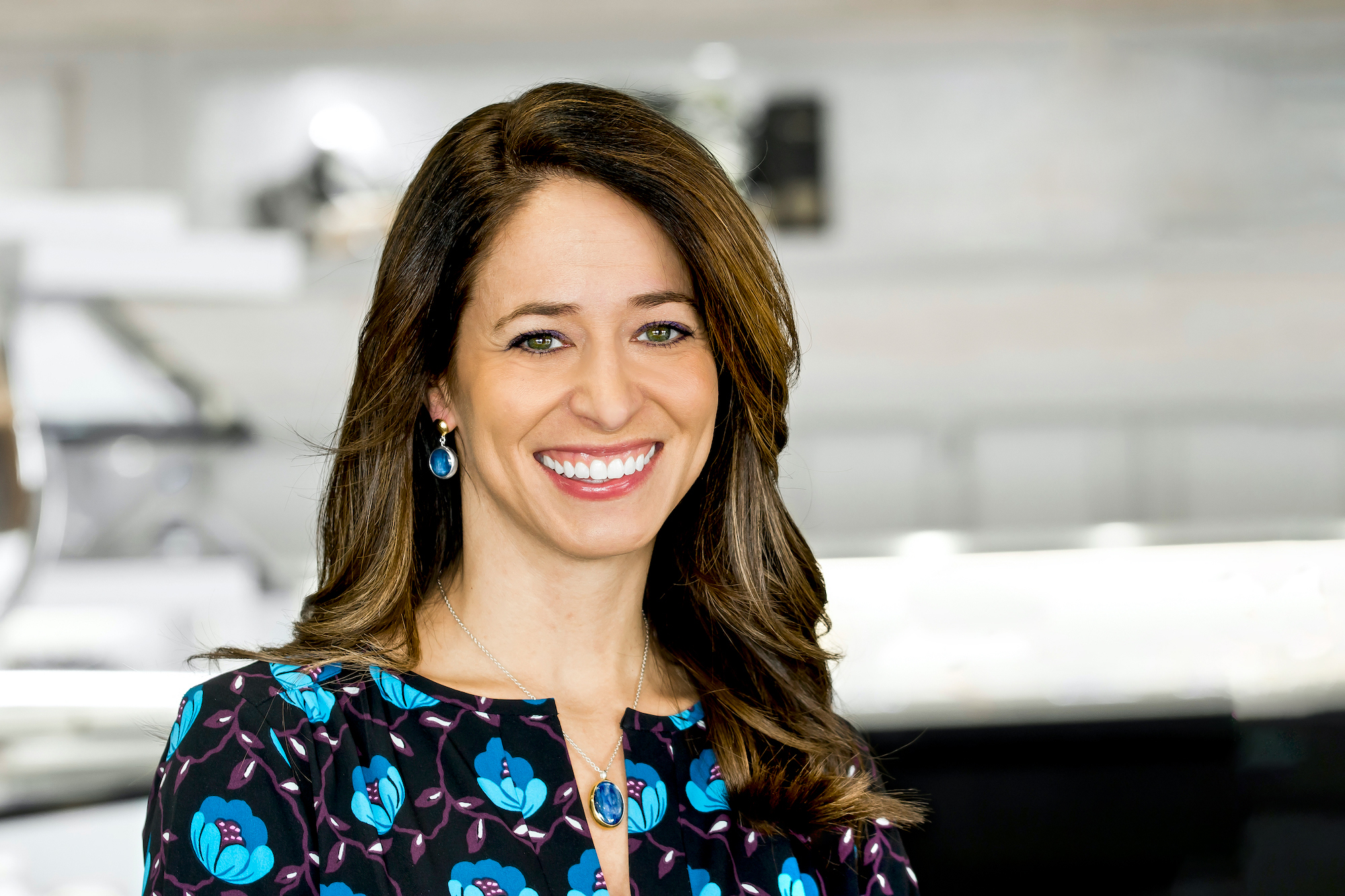 Headshot of Sales Manager Missy Ranney. With long brown hair and a big smile she is looking at the camera wearing a shirt with blue flowers and blue tear drop earrings.