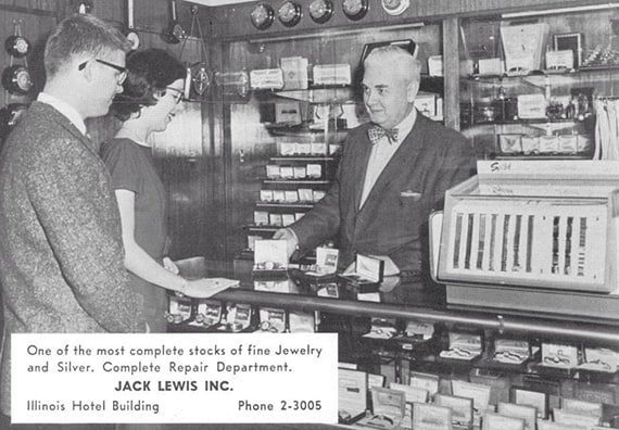 Black and white photo of original owner Jack Lewis behind the counter selling jewelry to a young couple in the 1930s
