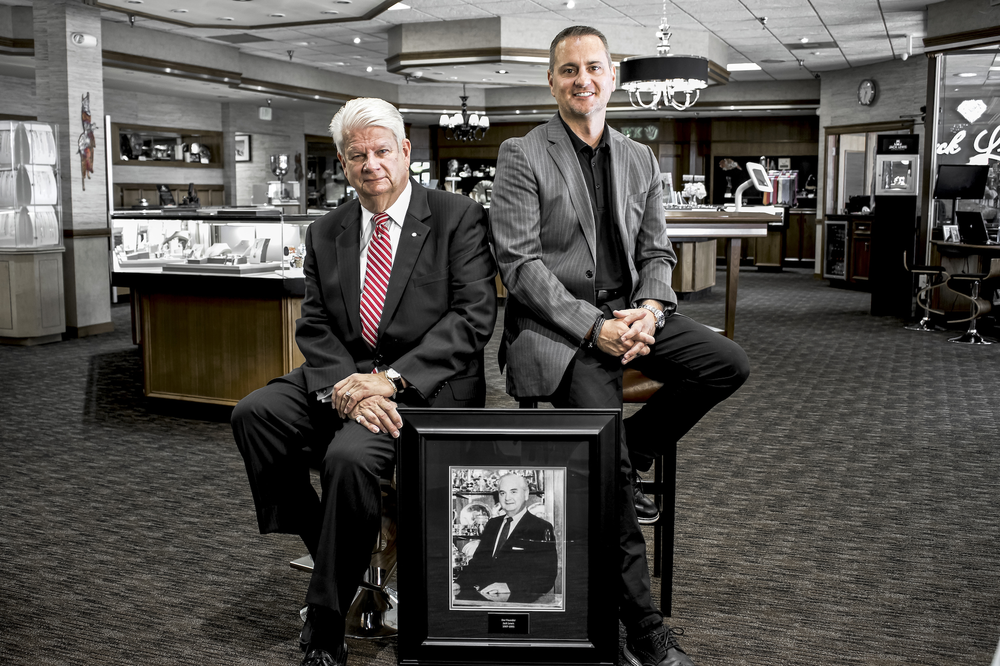 a black and white framed portrait of original owner Jack Lewis is situated behind the 2nd CEO John Wohlwend and the the current CEO John Carter