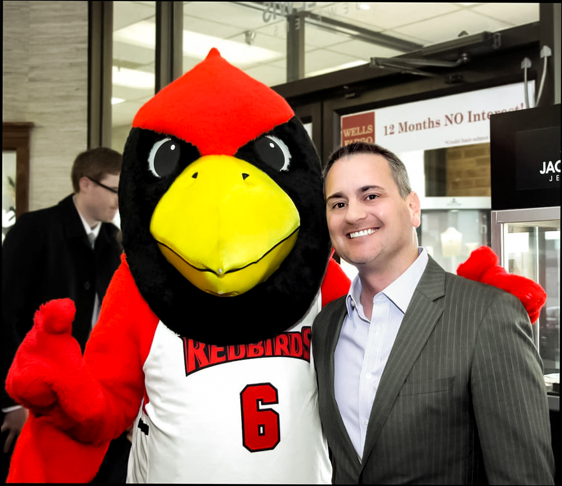 a younger CEO John Carter posing with Reggie the Redbird, the mascot of Illinois State University