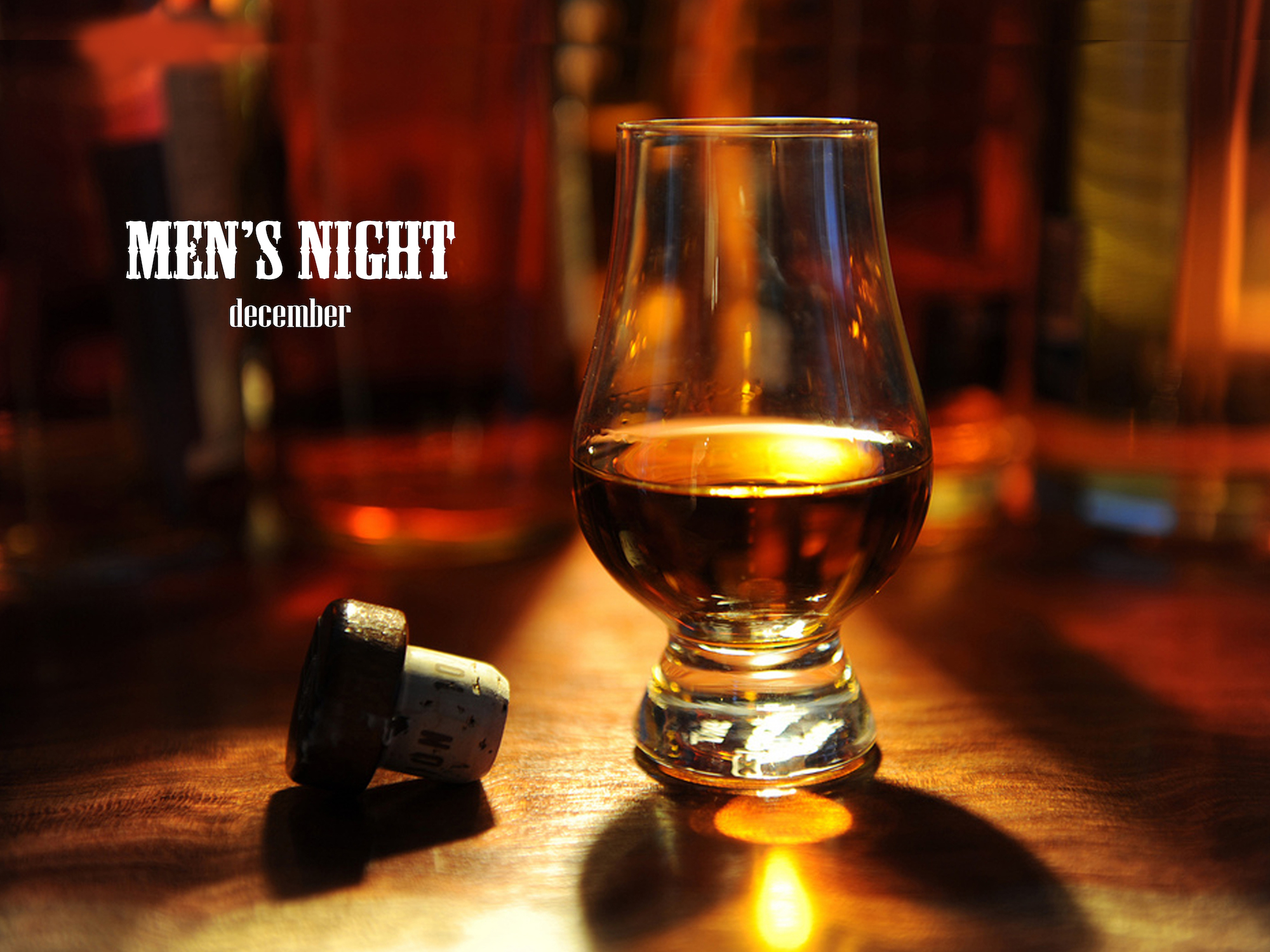 Glass of whiskey on a table with a cork nearby, warm shadowy lighting and the words Men's Night December