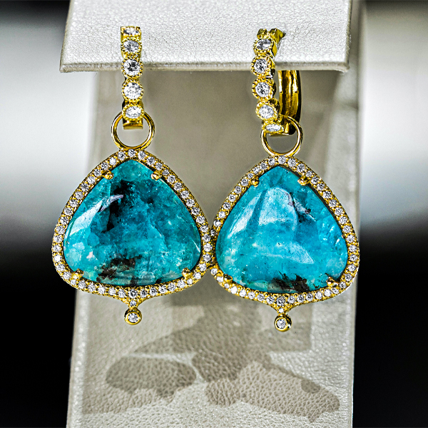 pair of teal teardrop earrings set in gold with diamond around the edges