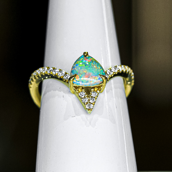 multicolored opal ring in a triangle shape mounted in a gold ring with diamond edging