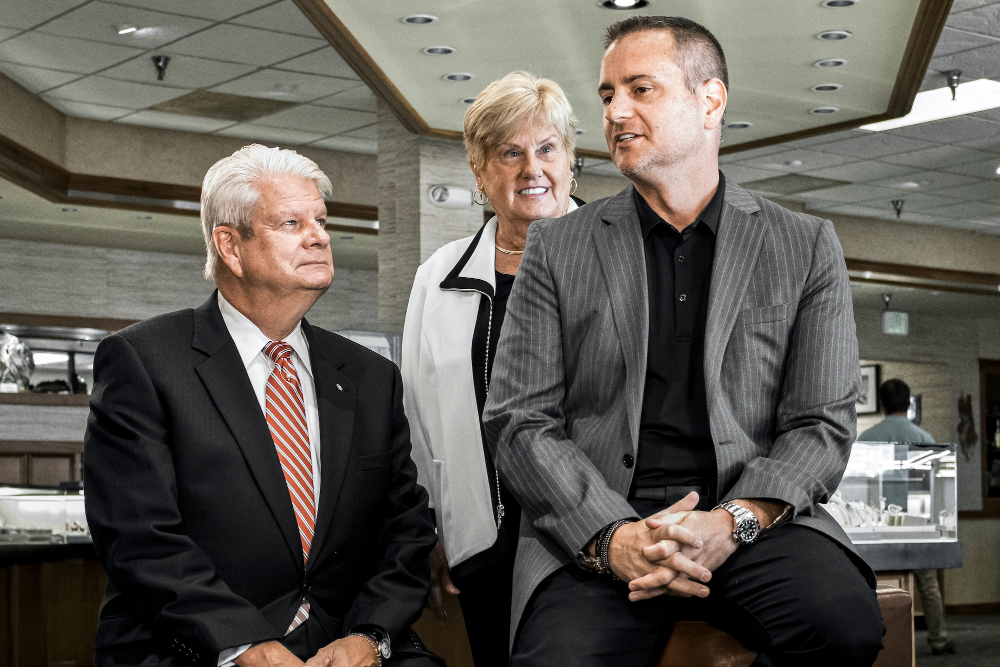 CEO John Carter sitting with former CEO John Wohlwend and his wife inside the Jack Lewis Jewelers store location