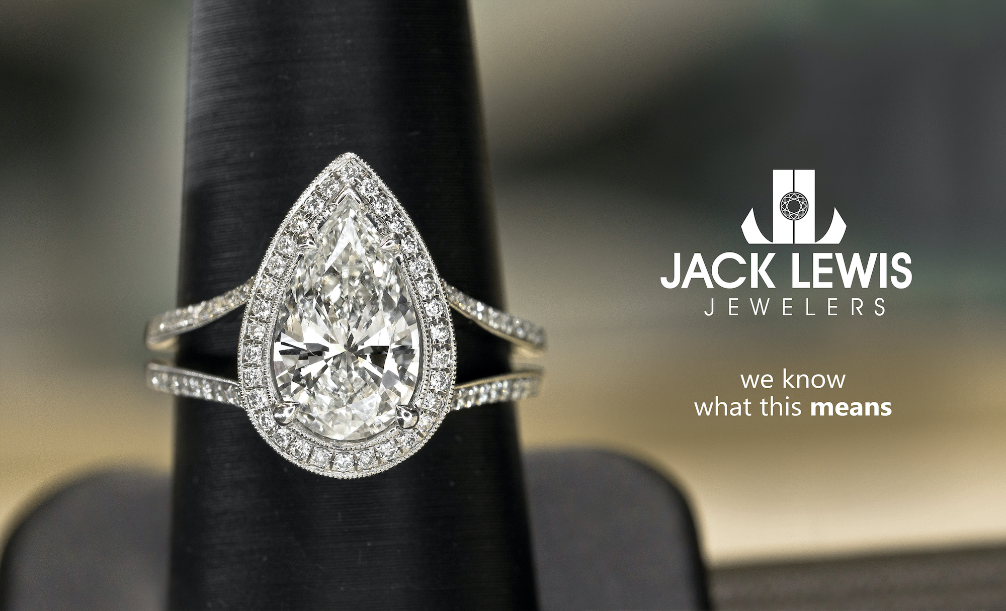 """Advertising billboard with a large pear shaped diamond engagement ring set in white gold. It sits next to the Jack Lewis Jewelers logo and has the phrase """"we know what this means"""""""