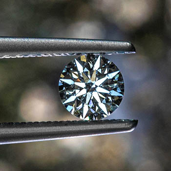 A round diamond held between two tweezers. When the image is tapped it reveals a heatmap of the same diamond displaying the symmetry of the cut of the diamond and it's clarity.