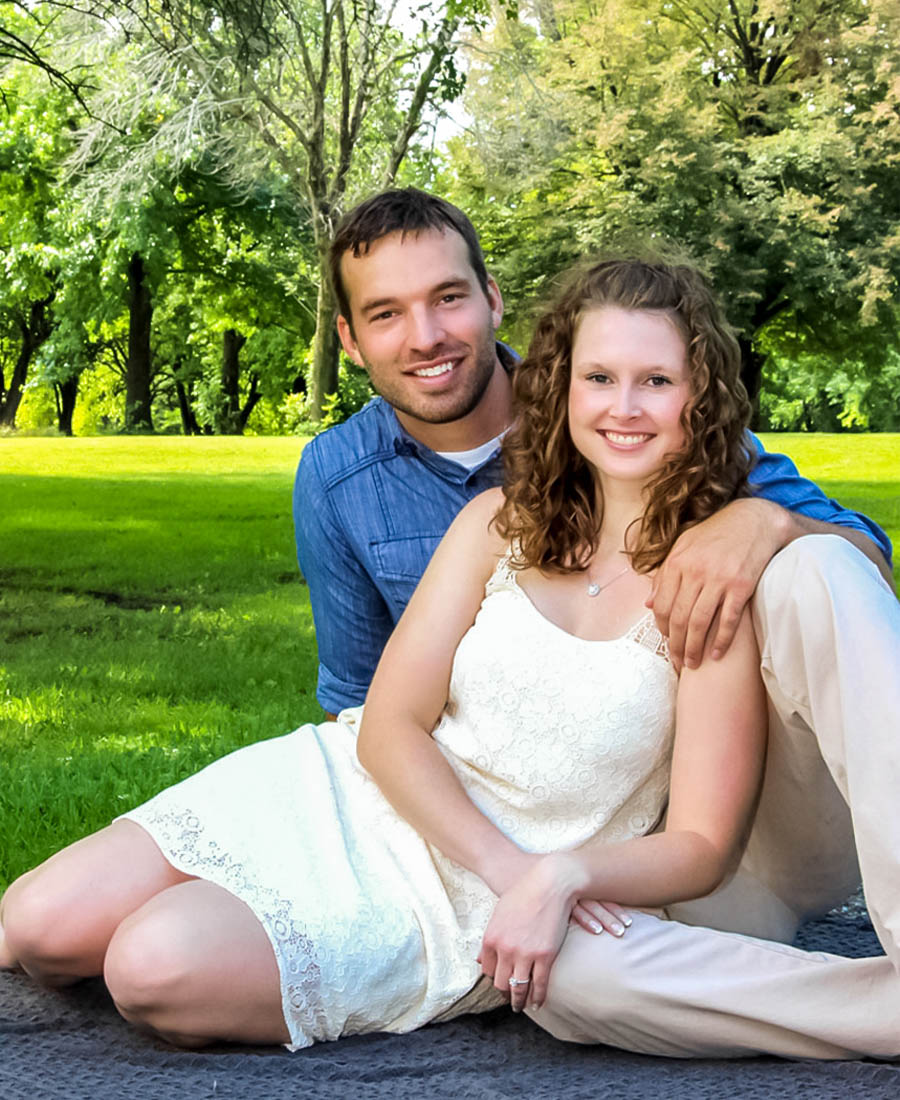 newly engaged couple sitting on the ground in the middle of a park