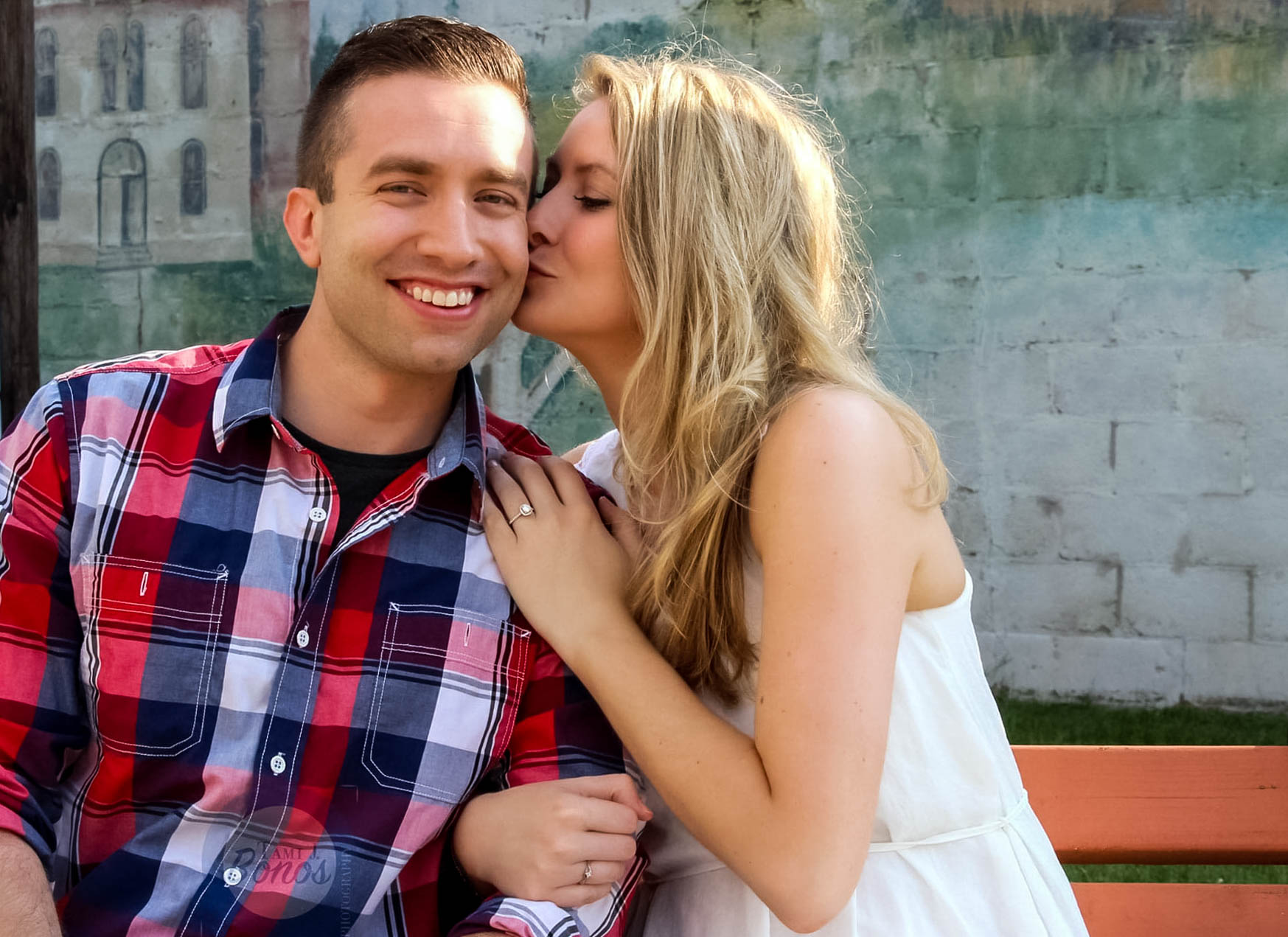 photoshoot of a newly engaged couple on a bench in front of a wall with a painted mural