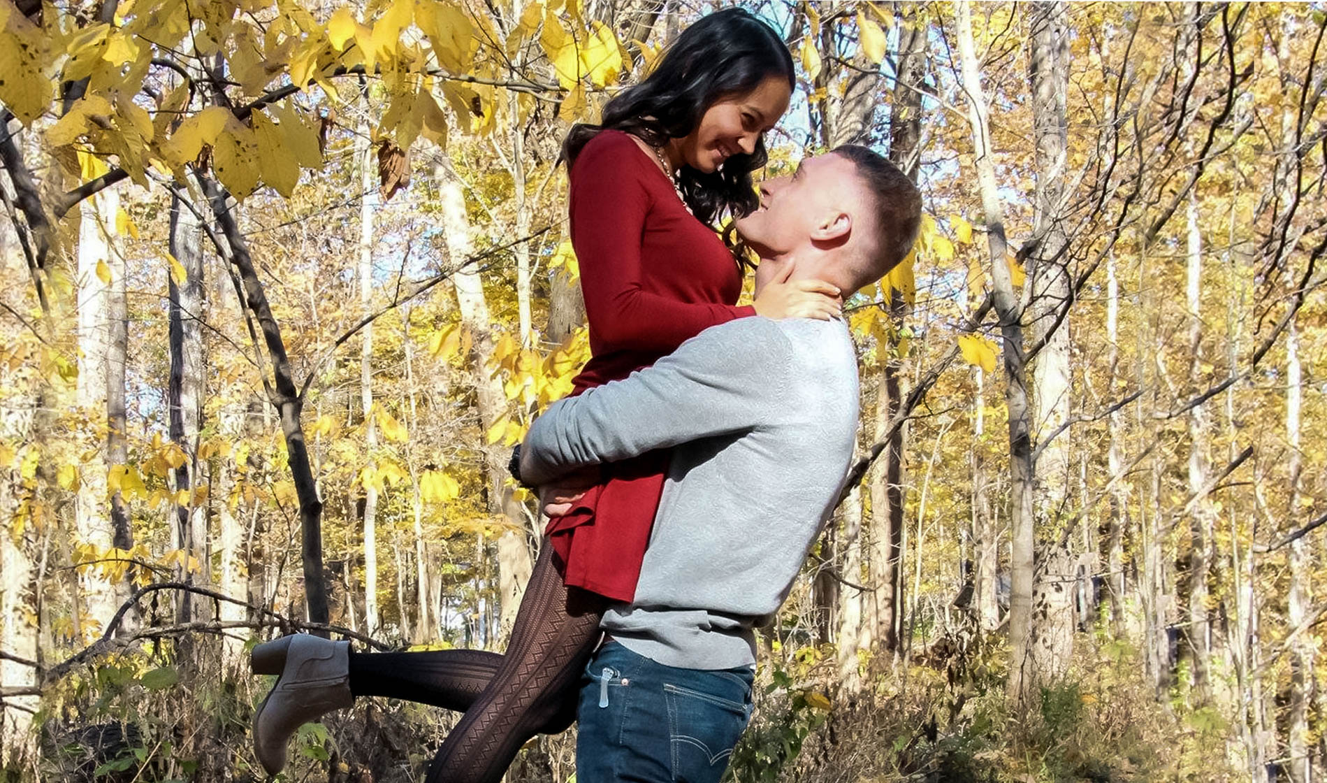 a newly engaged couple in the woods during autumn
