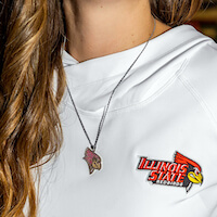 Close Up of a white Illinois State University Sweatshirt, with the Redbird logo in red and yellow. The woman wearing the sweatshirt is also wearing a custom necklace with the Redbird logo.