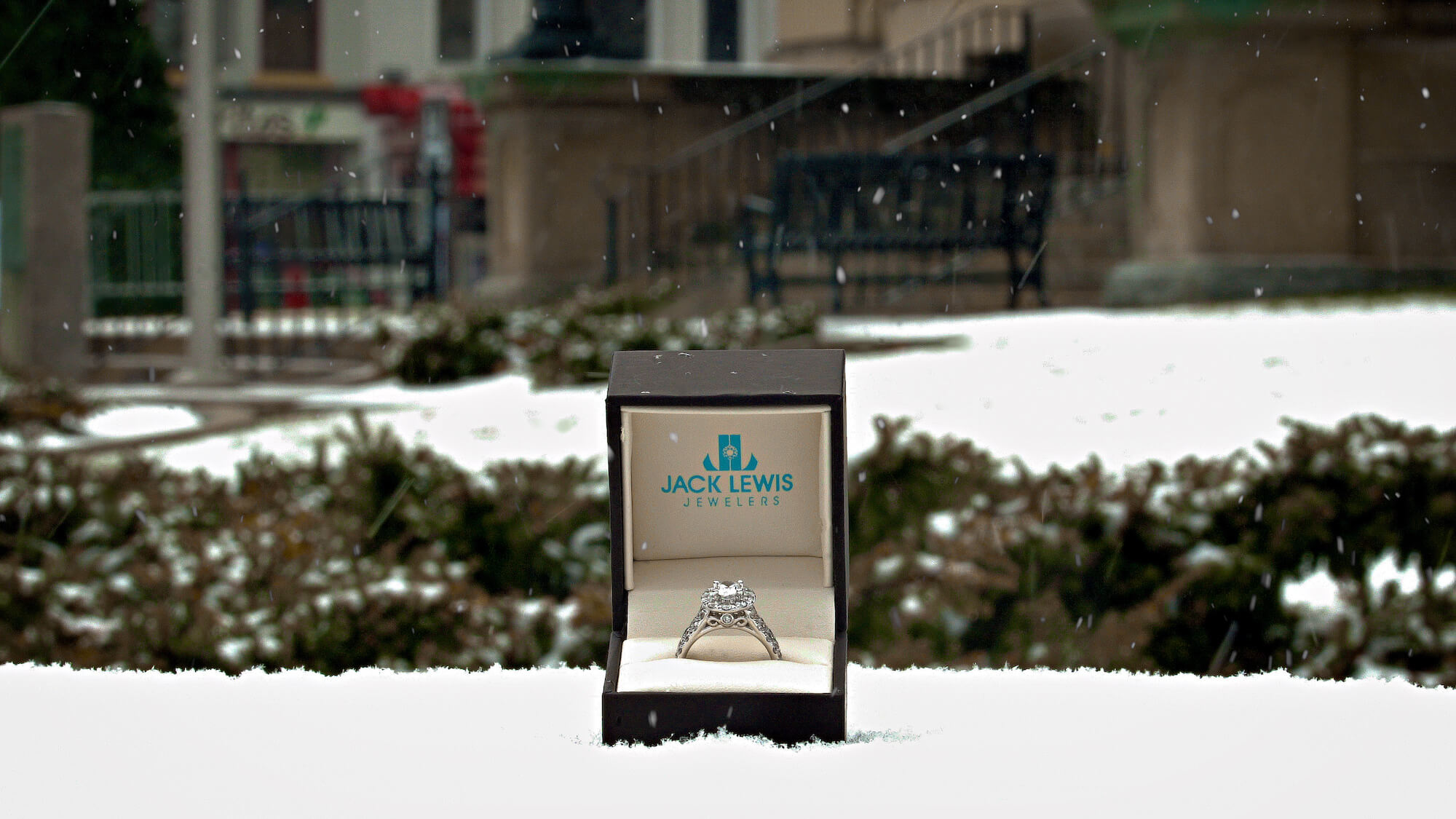 Diamond engagement ring inside an open Jack Lewis Jewelers ring box, sitting on a snowy ledge in front of the McLean County courthouse while is snows.
