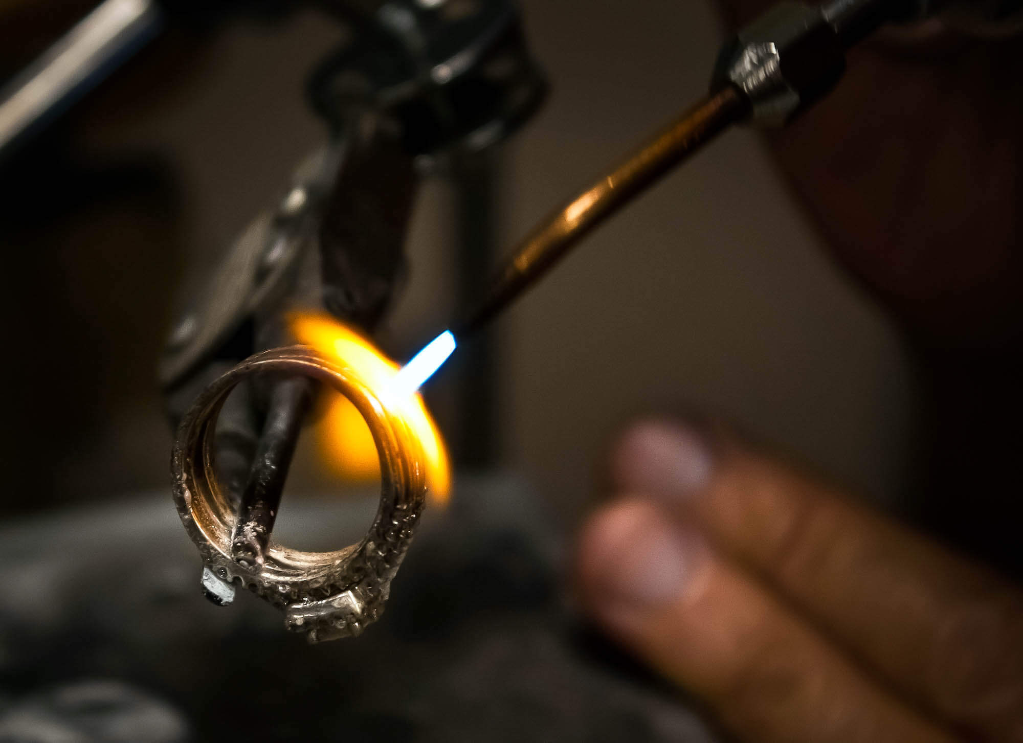 Close up of a man from the jewelry repair shop applying fire to a wedding band.