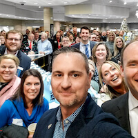 Group Selfie of members of the McLean County Chamber from 2019 inside of the Jack Lewis Jewelers store with John Carter the owner in the foreground.