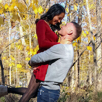 A newly engaged couple in the woods in the fall as the leaves are turning yellow. He lifts her up and they smile lovingly at each other.
