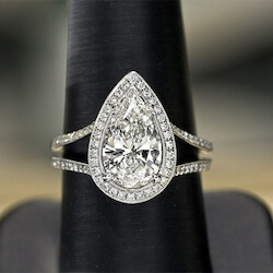 a pear shaped engagement ring in white gold on a holder