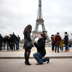 man on one knee proposing to brunette women in front of the Eiffel Tower in Paris, France