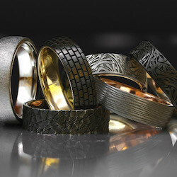 pile of men's wedding bands on a reflective surface