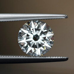 close up picture of round diamond being held by tweezers