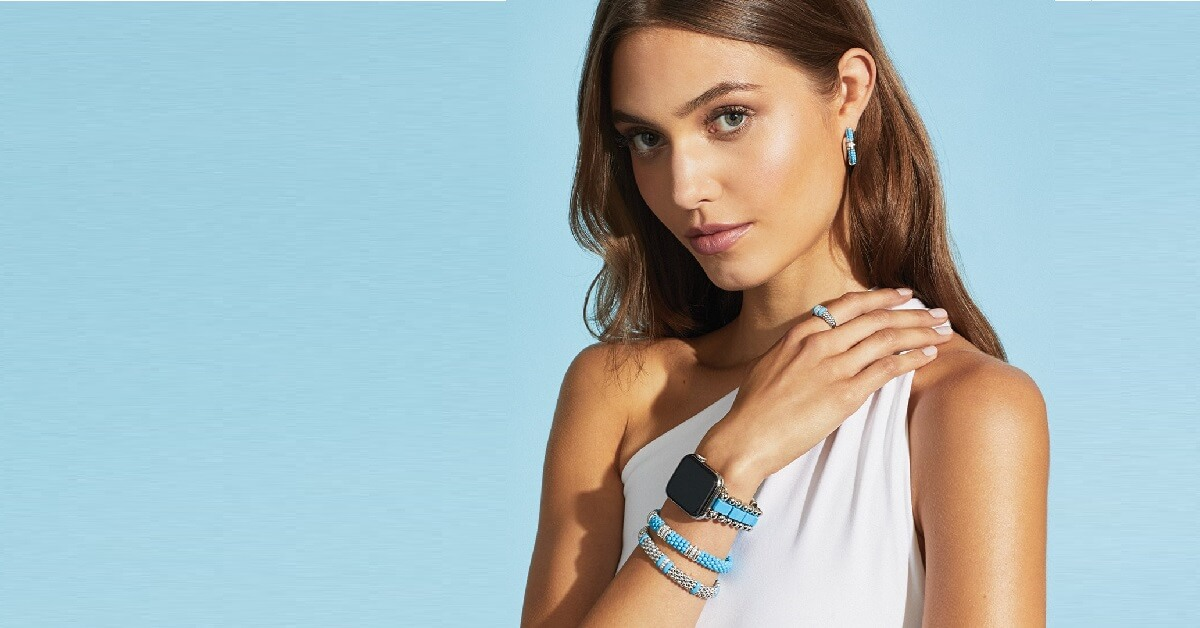 young woman with long brown hair, with her arm crossed over her shoulder revealing two bracelets, a watch, a ring and an earring all by Lagos. She is wearing a white shirt and is on a light blue background