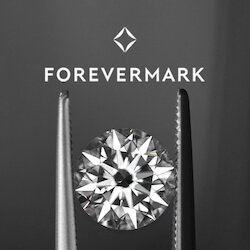 zoomed in brilliant round diamond held with tweezers below the Forever logo with a dark gray background