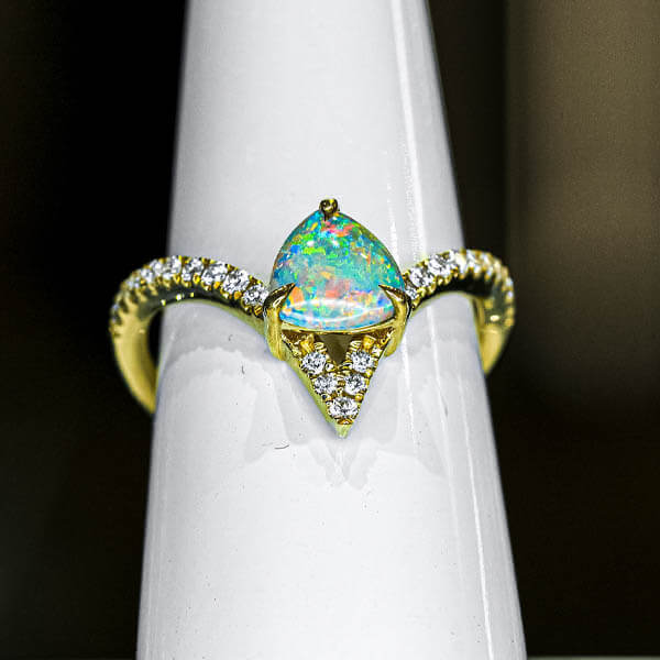 multi colored opal in a rounded triangle shape mounted in a gold ring with diamonds on the band