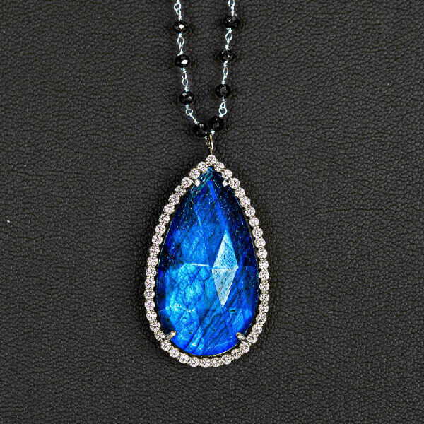 a blue gemstone in a teardrop shape placed within a gold rimmed pendant necklace