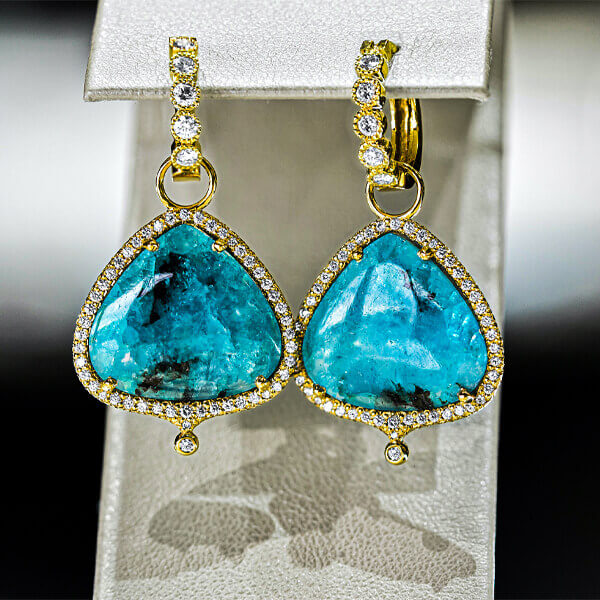 pair of teal tear drop shaped gemstones placed within a set of gold earrings