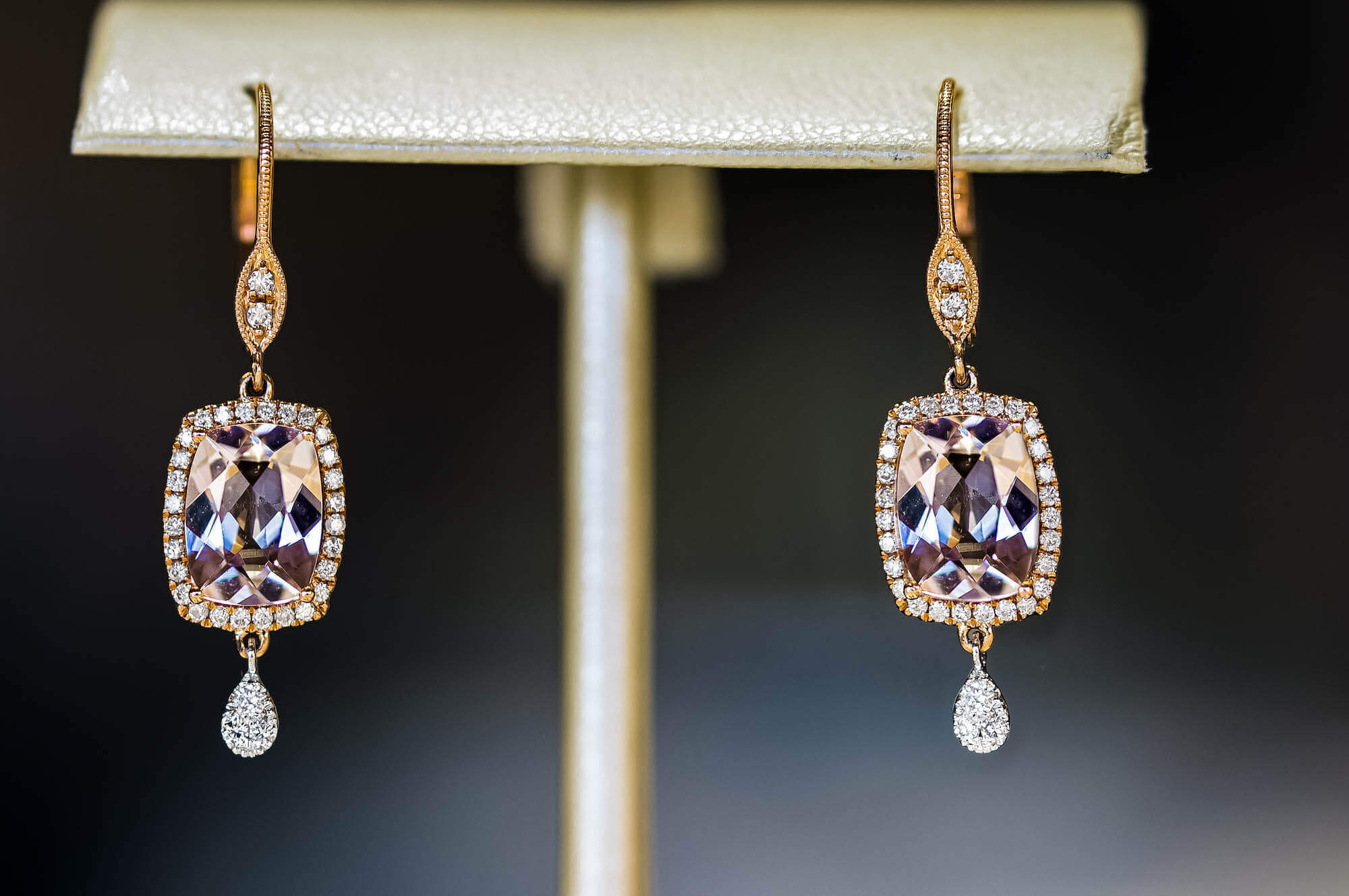 pair of light purple rectangular gemstones set in a pair of earrings. gemstone is surrounding with diamonds, and the top and bottom of each earring have an additional diamond