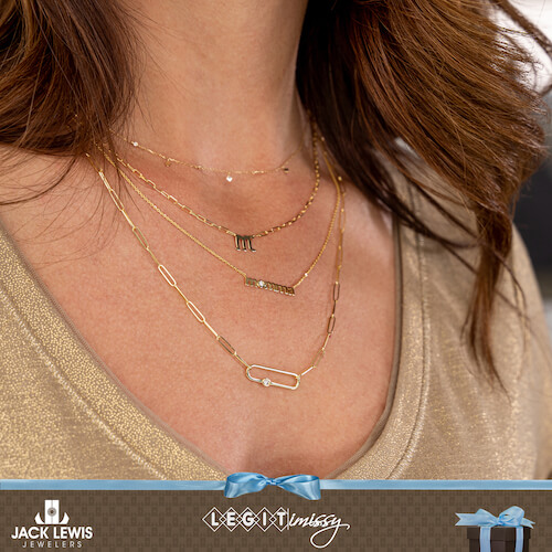 Missy wearing 4 layered gold necklaces. One says Momma, one has a diamond, another has a rectangular pendant.