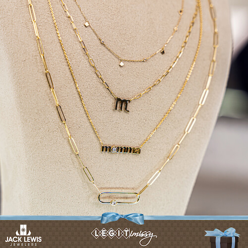 4 layered gold necklaces. One says Momma, one has a letter M, one has several small gold pendants, another has a rectangular pendant with a diamond.