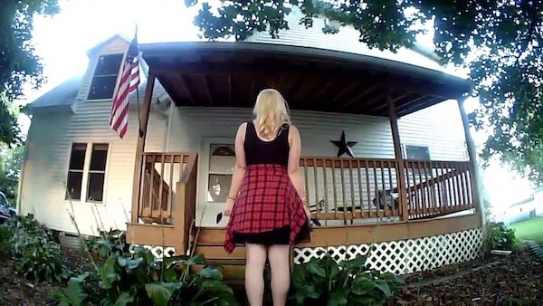 young woman with a flannel shirt wrapped around her waist is facing a front porch. We see her from behind and she appears to be waiting for something or someone.