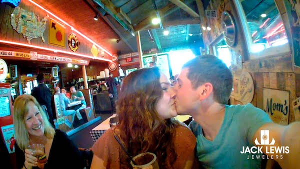 A young couple kiss after he proposes and she says yes. They are in a bar, an onlooker is smiling.